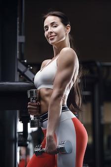 白いシャツのダンベルとジムでのトレーニングで運動フィットネスの女性。フィットネスとスポーツのコンセプト