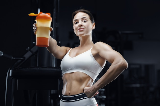 Athletic fitness woman drinking water from orange shaker at workout in the gym. pretty caucasian athletic girl. fitness and sport concept.