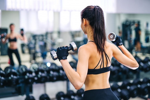 Athletic fitness woman pumping up muscles with dumbbells.