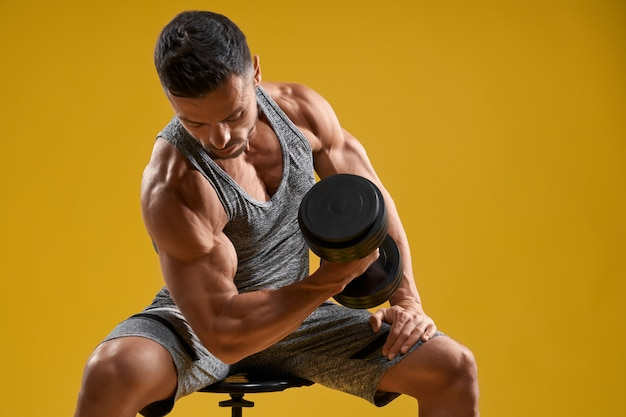 Athletic gentleman doing exercise with dumbbell