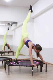 Спортивная девушка занимается прыжками на спортивном батуте