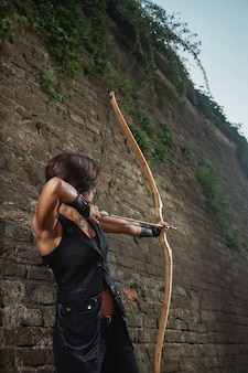Athletic girl in black shotting from big bow at side.