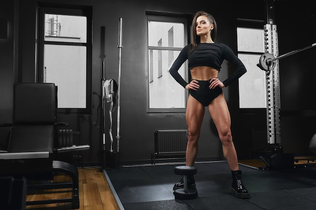 운동 소녀는 바벨과 웅크 리고 있습니다. 다리에 운동을하는 아름다운 피트니스 모델. 부하가있는 스쿼트를합니다. 목표에 도달하는 아름다운 다리.