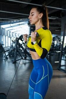 ジムでクロスオーバーで上腕二頭筋ケーブル カールをしている運動の女の子