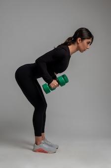 Athletic girl doing dumbbell triceps kickback on grey surface