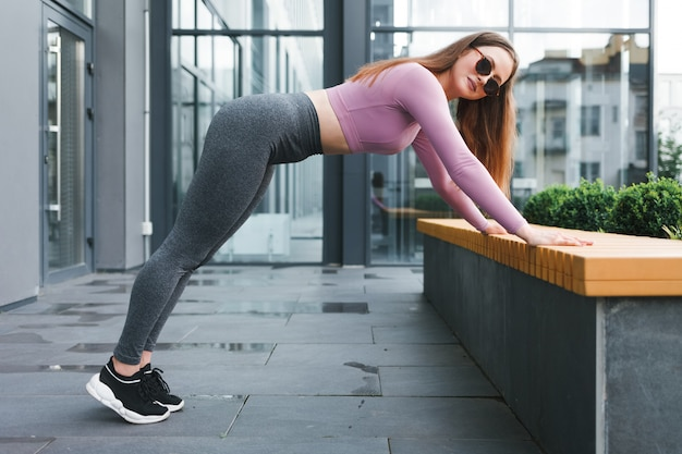 Athletic girl doing stretching outdoors