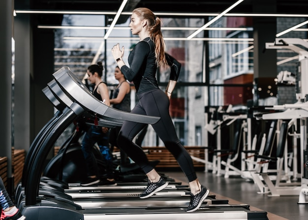 The athletic girl dressed in a black sportswear running on the treadmill in the modern gym .