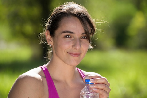 Athletic girl drinking water after exercising