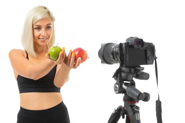 Спортивная девушка в спортивной форме показывает яблоки на камеру
