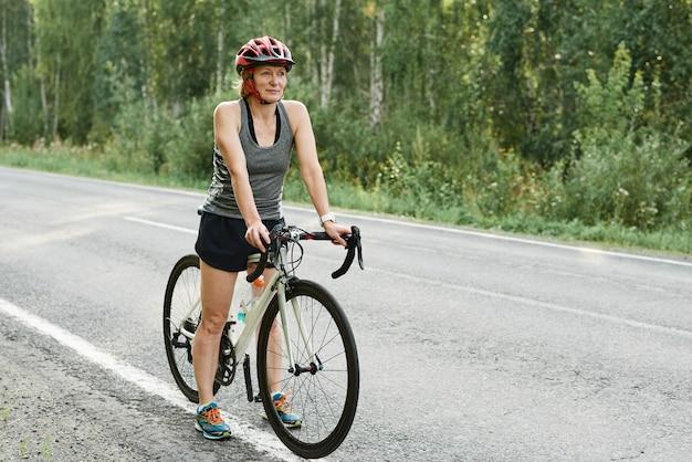 시골 길에서 스포츠 자전거를 타는 헬멧을 쓴 운동 소녀