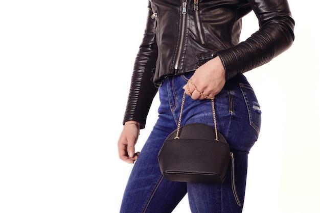 革のジャケットとジーンズの運動少女はチェーンに財布を保持します