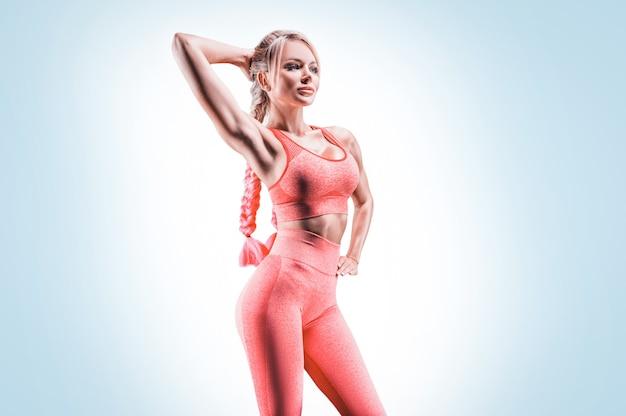 Спортивная (ый) девушка в розовой спортивной форме тренируется в тренажерном зале. концепция фитнеса