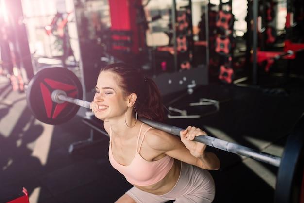 운동복에 체육 소녀는 바벨, 아령 운동을 수행합니다. 피트니스, 운동, 건강한 라이프 스타일