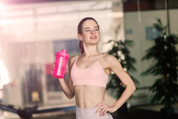 スポーツウェアのアスリートの女の子は、バーベル、ダンベルで運動を行います。フィットネス、健康的なライフスタイル