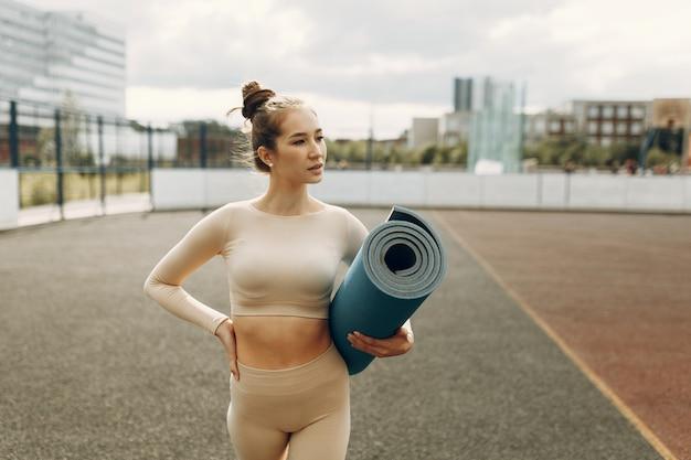 매트에 운동 소녀 워밍업입니다. 스트레칭과 함께 경기장에서 훈련.