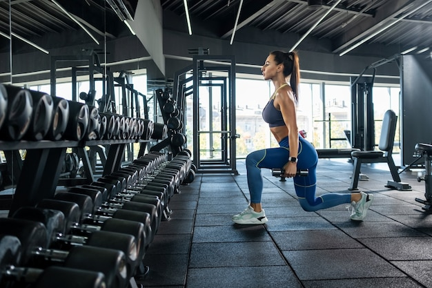 Athletic girl performing lunge with dumbbells at gym
