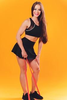 체육 소녀 저항 밴드를 사용하여 운동을 수행합니다. 배경에 어린 소녀의 사진입니다. 힘과 동기 부여.