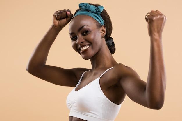 Атлетическая девушка позирует и показывает мышцы