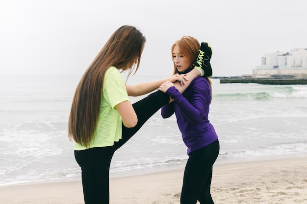 Athletic girl in sportswear help each other to do stretching on the beach on a cloudy day