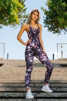 Спортивная девушка стоит на ступеньках парка в кроссовках и облегающем комбинезоне.