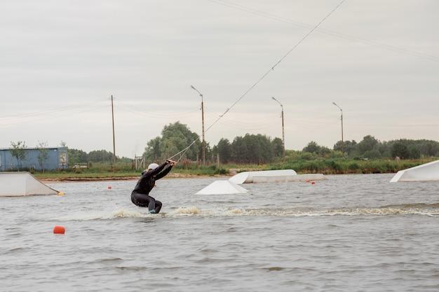 Спортивная девушка плавает на вейкборде. женщина на озере плывет на вейкборде. спортивная фотосессия.