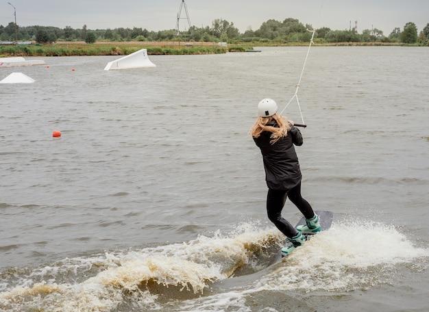 Спортивная девушка плавает на вейкборде. женщина на озере плывет на вейкборде.