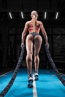 체육 소녀는 특별한 로프와 함께 체육관에서 훈련합니다. 다시보기. 스포츠, 피트니스, 에어로빅, 보디 빌딩, 스트레칭의 개념.