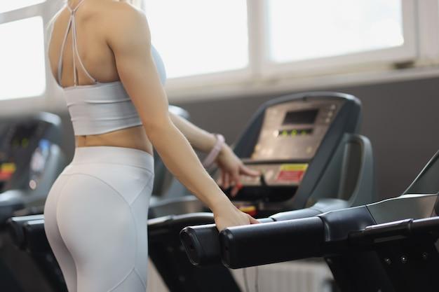 Спортивная (ый) девушка включает беговую дорожку для концепции бега в тренажерном зале