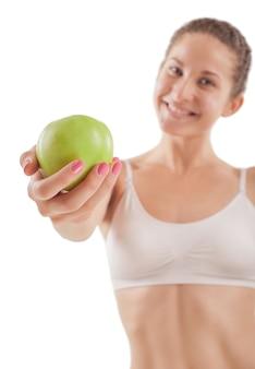 Спортивная (ый) девушка с зеленым яблоком в руке.