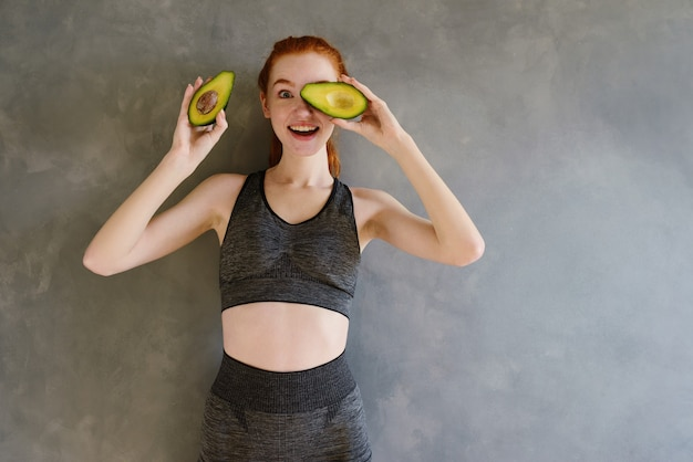 Athletic girl with gym clothes eats avocado at home