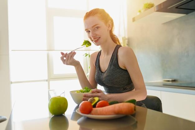 체육관 옷 운동 소녀는 부엌에서 샐러드를 먹는다