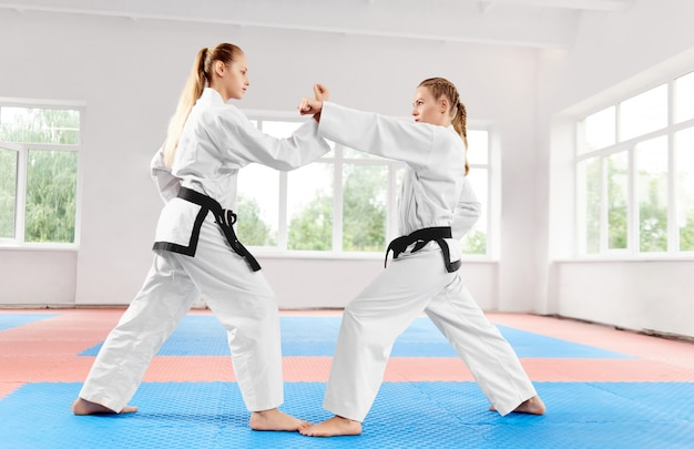 Athletic girls struggling using karate techniques in light karate class.