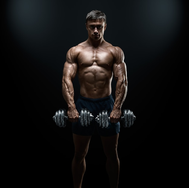 Athletic guy bodybuilder doing exercises with dumbbell