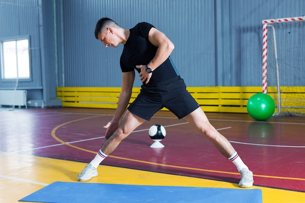 Спортивный парень в спортивной одежде и фитнес-трекере делает упражнения в тренажерном зале.