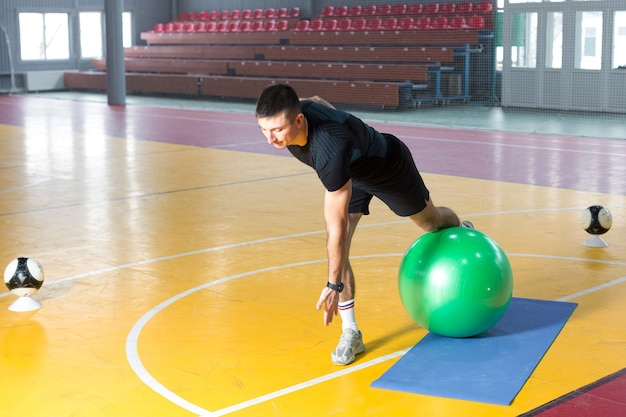 Athletic guy in sportswear and fitness tracker doing exercises in gym.