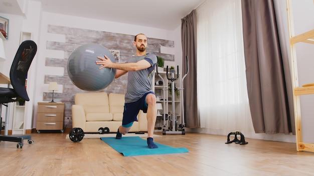 거실에 있는 요가 매트에서 집에서 스위스 공을 사용하여 운동하는 남자가 다리를 훈련합니다.