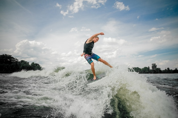 Athletic guy wakesurfing on the board down the river against the sky