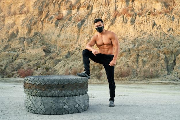 Спортивный парень в защитной маске и черных штанах, опираясь одной ногой на тяжелые шины на песчаном карьере. молодой человек без рубашки позирует и смотрит в камеру на открытом воздухе.