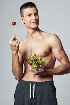 野菜サラダ灰色の背景を食べる筋肉の胴体を持つ運動選手