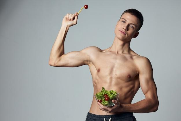 筋肉質の胴体を持つ運動選手は、彼の手の食事エネルギートレーニングでサラダのプレートを保持します