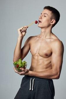 ポンプアップされた胴体の健康食品サラダプレート食事トレーニングを持つ運動選手