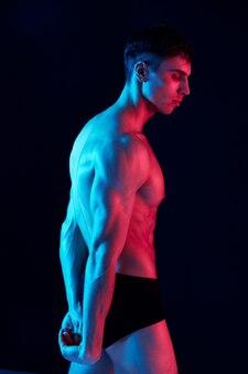 Спортивный парень со спортивным телосложением на черном фоне, вид сбоку, неоновый свет