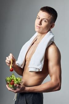 サラダ健康食品ボディービルダーの筋肉の胴体プレートを持つ運動選手