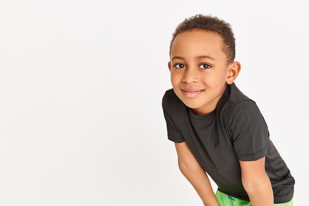 Спортивный красивый афро-американский мальчик делает беговые упражнения, глядя в камеру со счастливой улыбкой, имея перерыв, чтобы восстановить дыхание