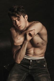裸の胴体と黒い壁に黒いジーンズでポーズをとって運動のハンサムなブルネット男。