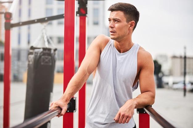 アスレチックハンサムな男は、鉄棒で運動し、通りの屋外で上半身をトレーニングしています
