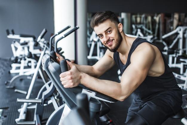 Спортивный (ый) красивый мужчина делает тренировки на трассе в современном тренажерном зале