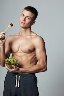 アスレチックハンサムな男筋肉胴体プレートサラダ健康ダイエット