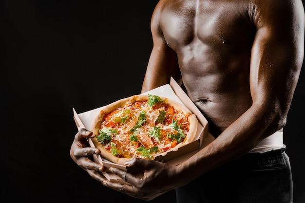 黒人男性のアスレチックハンサムな裸の体はピザ配達で働いています