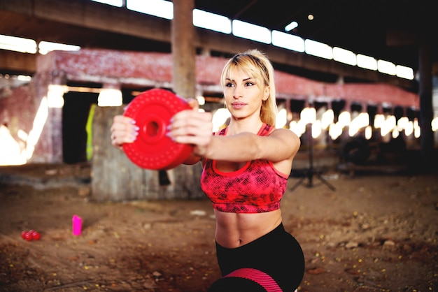 古い格納庫でダンベルでスクワットを行う運動の健康な女性。